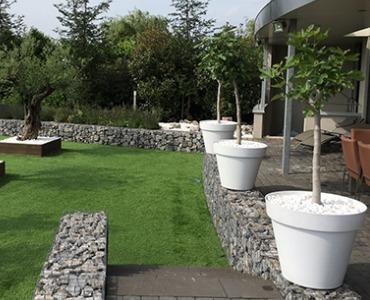 Moderne Gartengestaltung mit Pflanzen, Möbeln und Steinen